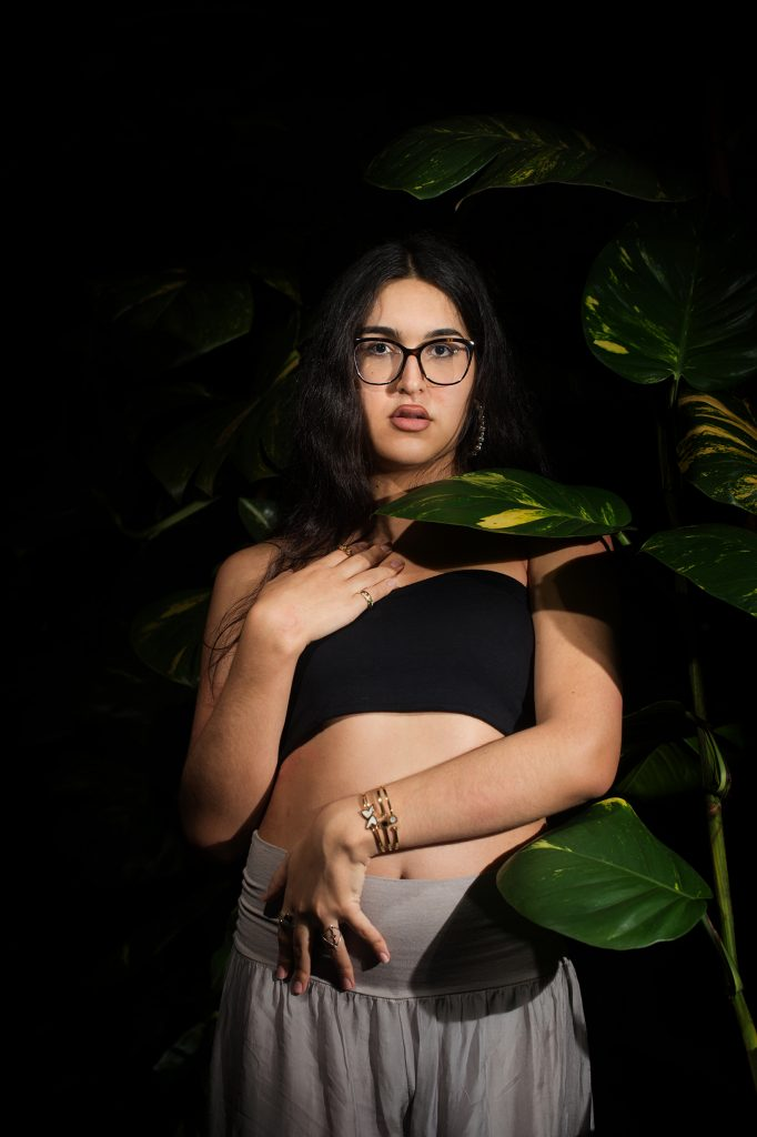 Fundo escuro com plantas verdes, mulher trans branca, cabelos compridos pretos, semblante neutro, óculos de grau, croped preto, calça cinza.