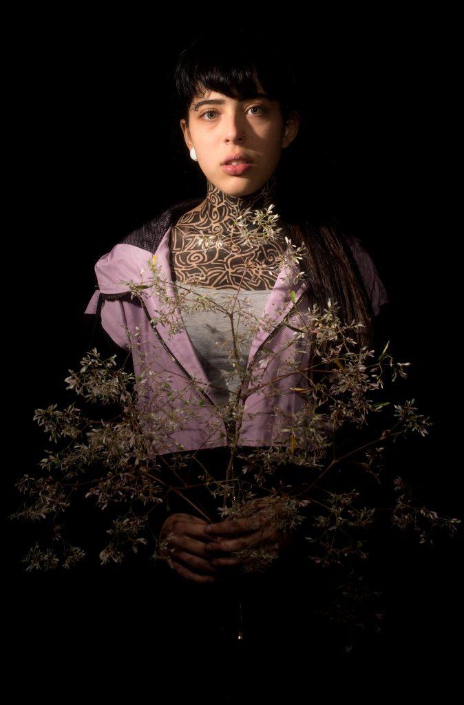 Fundo escuro, mulher branca, cabelo curto, semblante neutro, jaqueta em tons de rosa e preto, segurando um ramo de planta em forma de um triangulo.